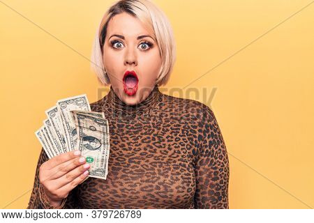 Beautiful blonde plus size woman holding bunch of dollars banknotes over yellow background scared and amazed with open mouth for surprise, disbelief face