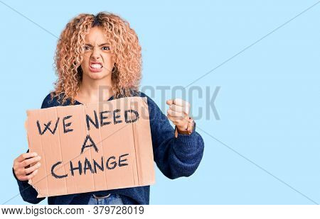 Young blonde woman with curly hair holding we need a change banner annoyed and frustrated shouting with anger, yelling crazy with anger and hand raised