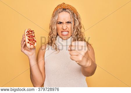 Young beautiful blonde woman eating fast food hot dog with ketchup and mustard annoyed and frustrated shouting with anger, yelling crazy with anger and hand raised