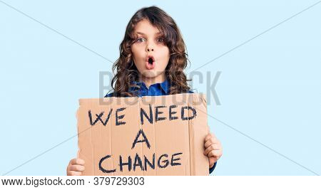Cute hispanic child with long hair holding we need a change banner scared and amazed with open mouth for surprise, disbelief face