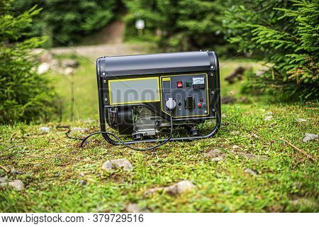Portable Gasoline Generator In The Open Air, In Nature.