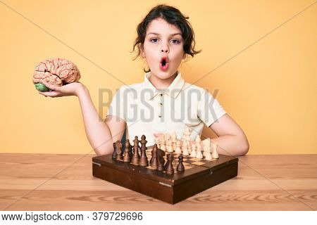 Cute hispanic child holding brain while playing chess scared and amazed with open mouth for surprise, disbelief face