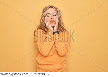 Young beautiful blonde sporty woman wearing casual sweatshirt over yellow background Tired hands covering face, depression and sadness, upset and irritated for problem