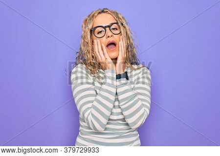 Beautiful blonde woman wearing casual striped t-shirt and glasses over purple background Tired hands covering face, depression and sadness, upset and irritated for problem