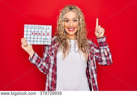 Young beautiful blonde woman holding period calendar controlling menstrual cycle surprised with an idea or question pointing finger with happy face, number one