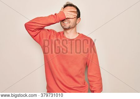 Young handsome man with blue eyes wearing casual sweater standing over white background smiling and laughing with hand on face covering eyes for surprise. Blind concept.