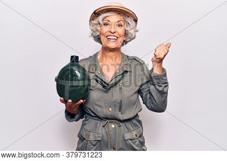 Senior grey-haired woman wearing explorer hat holding water canteen pointing thumb up to the side smiling happy with open mouth