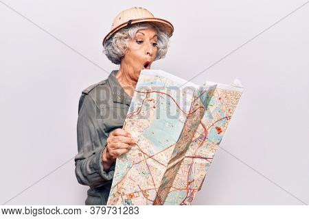 Senior grey-haired woman wearing explorer hat holding map scared and amazed with open mouth for surprise, disbelief face