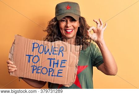 Middle age brunette communist woman holding banner with power to the people message doing ok sign with fingers, smiling friendly gesturing excellent symbol