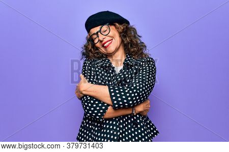 Middle age beautiful woman wearing casual jacket and french beret over purple background hugging oneself happy and positive, smiling confident. Self love and self care