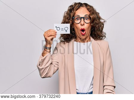 Middle age beautiful woman holding paper with gender equality concept message scared and amazed with open mouth for surprise, disbelief face