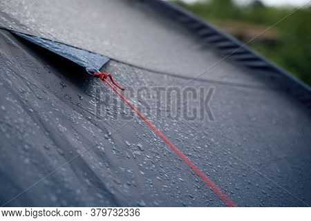 Closeup Detail Perspective View Of Anchoring Red Rope On Dark Blue Outdoor Waterproof Tent Covered I