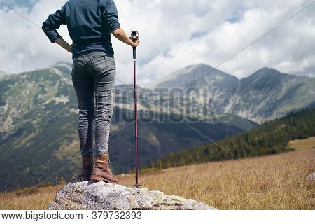 Rear View Of A Caucasian Woman With Hiking Stick Standing On A Large Stone And Enjoying The View Of