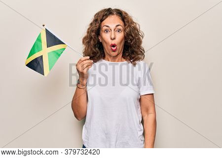 Middle age beautiful tourist woman holding italian flag over isolated white background scared and amazed with open mouth for surprise, disbelief face