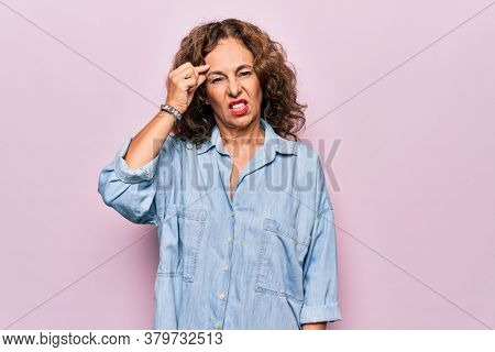 Middle age beautiful woman wearing casual denim shirt standing over pink background worried and stressed about a problem with hand on forehead, nervous and anxious for crisis
