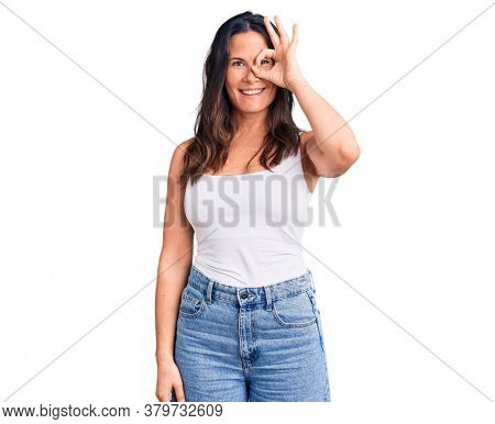 Young beautiful brunette woman wearing casual sleeveless t-shirt doing ok gesture with hand smiling, eye looking through fingers with happy face.