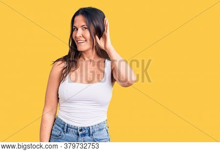 Young beautiful brunette woman wearing casual sleeveless t-shirt smiling with hand over ear listening an hearing to rumor or gossip. deafness concept.