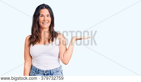 Young beautiful brunette woman wearing casual sleeveless t-shirt smiling cheerful presenting and pointing with palm of hand looking at the camera.
