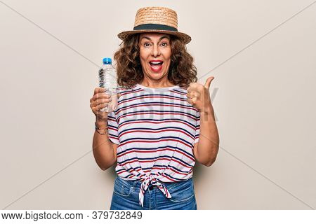Middle age beautiful woman wearing hat drinking bottle of water over white background pointing thumb up to the side smiling happy with open mouth