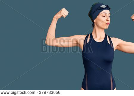 Young beautiful hispanic woman wearing swimwear and swimmer glasses showing arms muscles smiling proud. fitness concept.