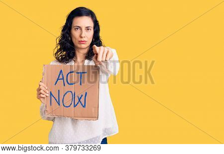 Young beautiful hispanic woman holding act now banner pointing with finger to the camera and to you, confident gesture looking serious