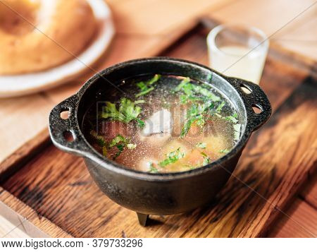Homemade Chicken Bouillon Or Broth With Meat Piece, Served Greens. Soup In Metal Rustic Bowl On Wood
