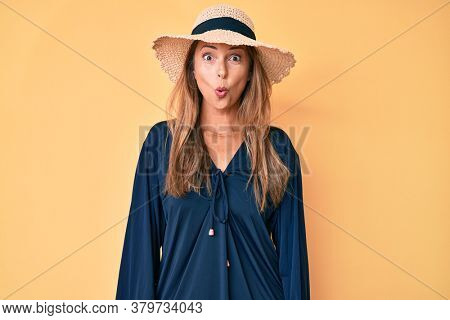 Middle age hispanic woman wearing summer hat scared and amazed with open mouth for surprise, disbelief face