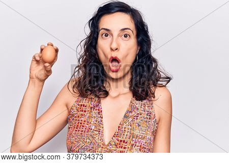 Young beautiful hispanic woman holding egg scared and amazed with open mouth for surprise, disbelief face