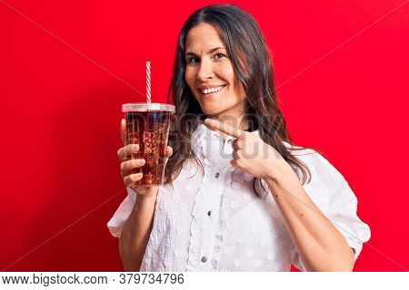Beautiful brunette woman drinking cola refreshment beverage using straw over red background smiling happy pointing with hand and finger