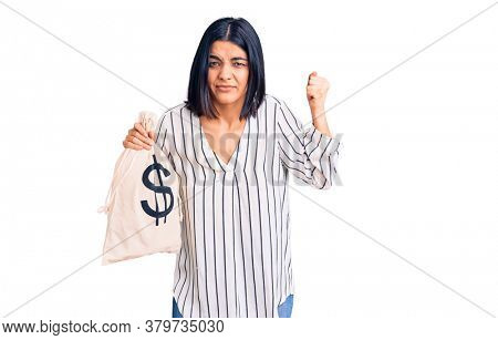 Young beautiful latin woman holding money bag with dollar symbol annoyed and frustrated shouting with anger, yelling crazy with anger and hand raised
