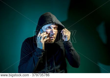 A Male Intruder With A Hood On His Head Is Talking On The Phone On A Dark Green Background