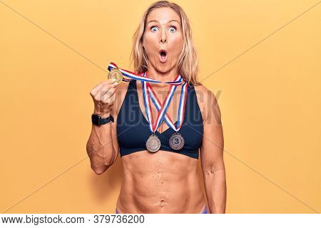 Middle age caucasian blonde woman wearing winner medals scared and amazed with open mouth for surprise, disbelief face