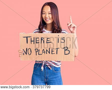 Young beautiful chinese girl holding there is no planet b banner surprised with an idea or question pointing finger with happy face, number one