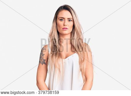 Young beautiful blonde woman wearing sleeveless t-shirt with serious expression on face. simple and natural looking at the camera.