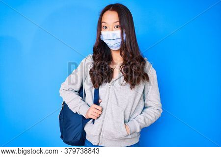 Young beautiful chinese girl holding student backpack wearing medical mask scared and amazed with open mouth for surprise, disbelief face
