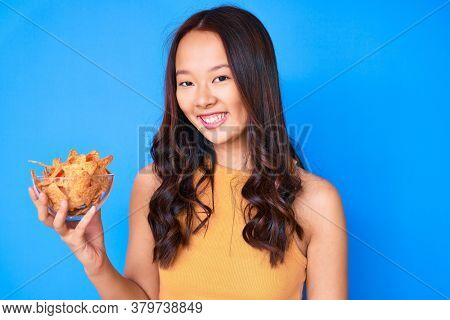 Young beautiful chinese girl holding nachos potato chips looking positive and happy standing and smiling with a confident smile showing teeth