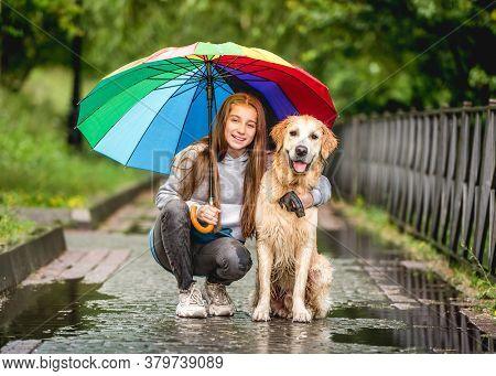Girl and golden retriever under umbrella