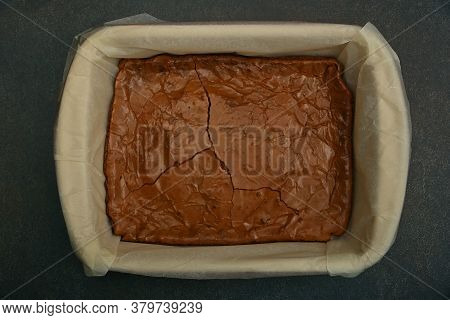Whole Fresh Baked Chocolate Cake In Baking Tin Form With Parchment On Table, Elevated Top View, Dire