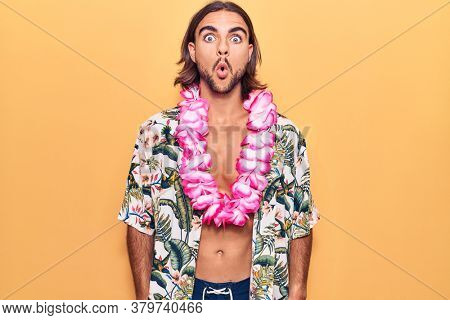 Young handsome man wearing swimwear and hawaiian lei scared and amazed with open mouth for surprise, disbelief face