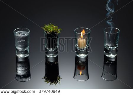 Four Elements Of Nature - Air, Fire,  Earth, Water. Four Elements Concept In Glasses On A Black Refl