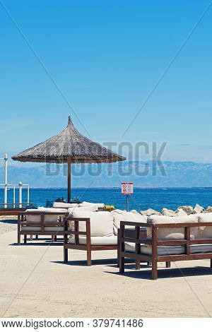 Wooden Lounge Bar Benches With Straw Umbrella By Adriatic Sea In Croatia On A Clear Sunny Day. No Do