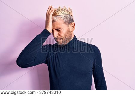 Young handsome blond man with piercing wearing golden king crown over pink background surprised with hand on head for mistake, remember error. Forgot, bad memory concept.