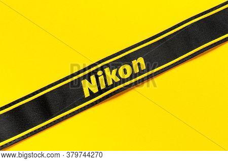 Moscow, Russia - July 15, 2020: Strap From Camera Nikon On Yellow Background Flat Lay. Digital Photo