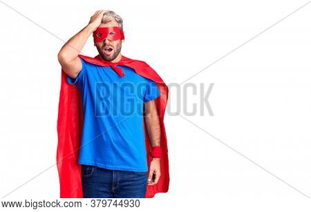 Young blond man wearing super hero custome surprised with hand on head for mistake, remember error. forgot, bad memory concept.