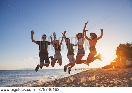 Group Of People Jumping On The Beach. Five Friends Have Fun On The Beach, Laughing And Haveing Fun A