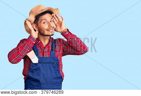 Handsome latin american young man weaing handyman uniform smiling cheerful playing peek a boo with hands showing face. surprised and exited