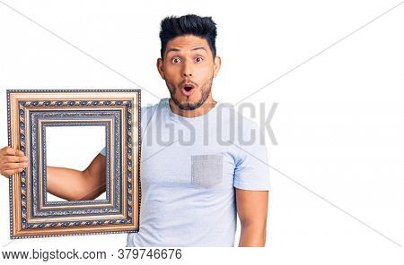 Handsome latin american young man holding empty frame scared and amazed with open mouth for surprise, disbelief face