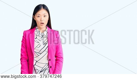 Young beautiful chinese woman wearing elegant clothes scared and amazed with open mouth for surprise, disbelief face