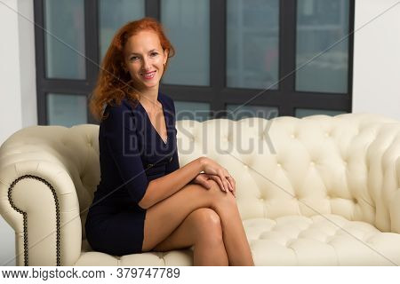 Beautiful Young Woman Sits On A Sofa In The Studio Near A Large Window.