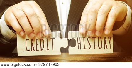 A Businessman Is Holding Wooden Puzzles With The Words Credit History. History Of Fulfillment By An